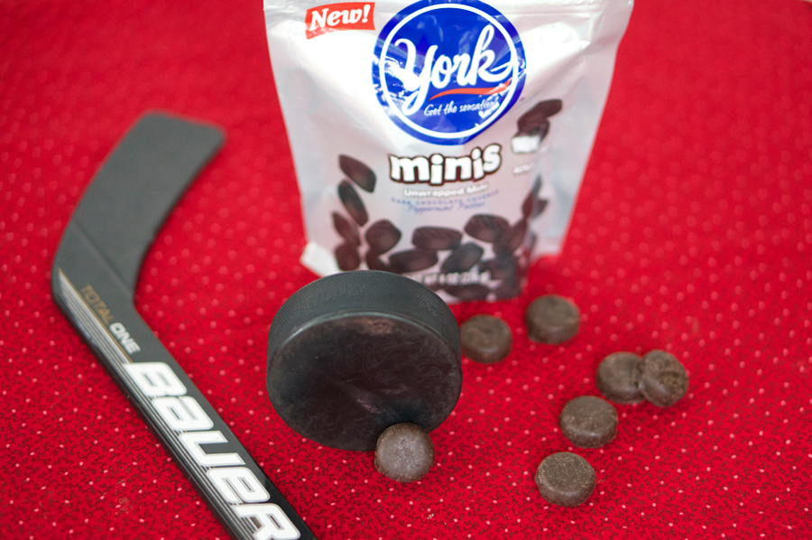 Mini York Peppermint Patties look like mini hockey pucks. The bite-sized treats are the perfect cupcake topper for a hockey party! | Sweeterville.com